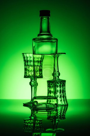 bottle of absinthe with lead glasses on reflective surface and dark green background