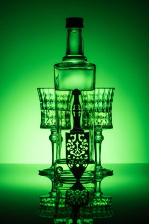 bottle of absinthe with crystal glasses on reflective surface and dark green background