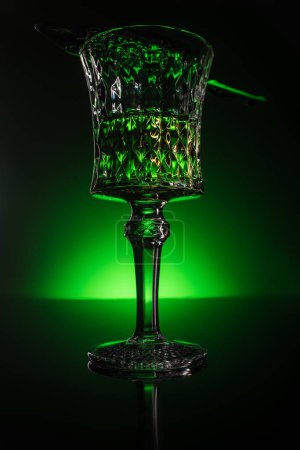 close-up shot of glass with absinthe on reflective surface and dark green background