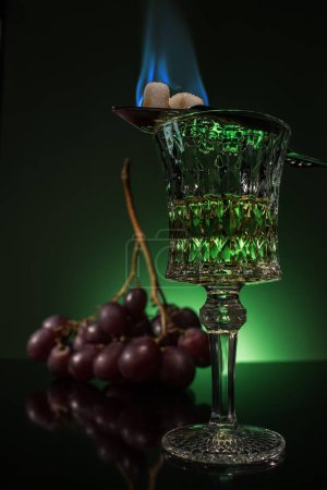 lead glass of absinthe with branch of grapes and burning sugar on spoon on reflective surface and dark green background