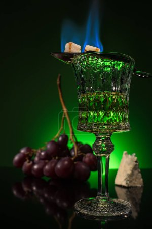 crystal glass of absinthe with branch of grapes and burning sugar on spoon on reflective surface and dark green background