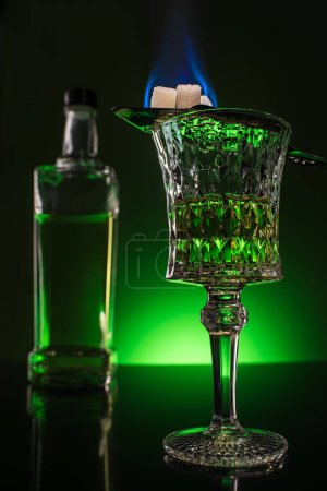 glass and bottle of absinthe with burning sugar on spoon on reflective surface and dark green background