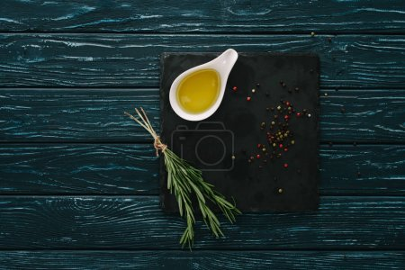Photo for Top view of rosemary, oil and pepper corns black stone slate on wooden tabletop - Royalty Free Image