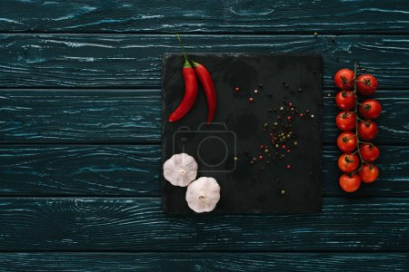 top view of vegetables and chilli peppers on stone cutting board on green wooden tabletop