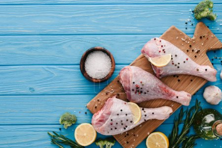 top view of turkey legs on wooden board with salt, lemon and rosemary on blue tabletop