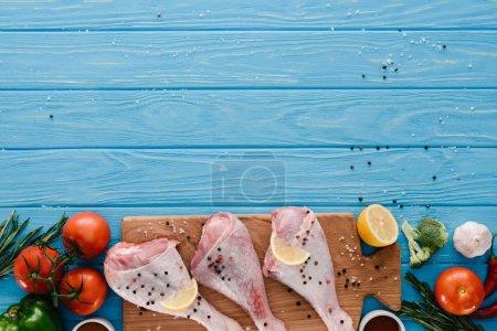 Photo pour Vue de dessus des cuisses de poulet sur une planche en bois avec différents légumes sur le dessus de table bleu - image libre de droit