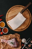 top view of raw turkey leg, spices and wooden cutting board with meat cleaver