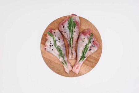 top view of raw chicken legs with pepper corns and rosemary on wooden cutting board, isolated on white