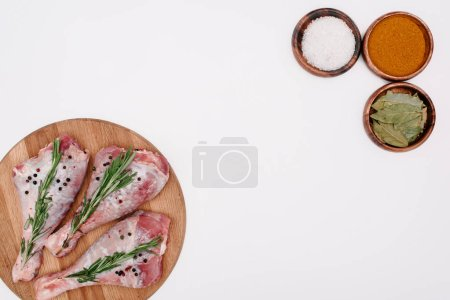 top view of raw turkey legs with rosemary on cutting board with salt, paprika and bay leaves in bowls, isolated on white
