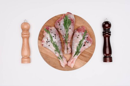 top view of uncooked turkey legs with rosemary, pepper and salt, isolated on white