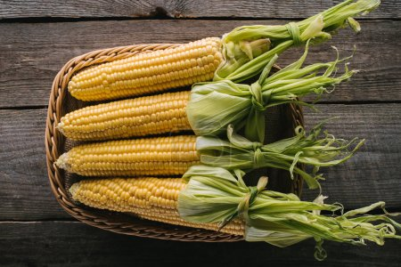 Photo for Top view of fresh raw corn cobs in basket on wooden tabletop - Royalty Free Image