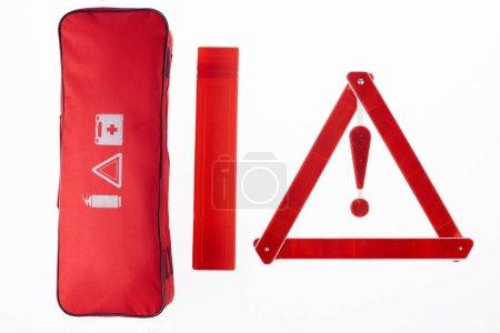 Draufsicht auf rotes Warndreieck und Handtasche isoliert auf weiß