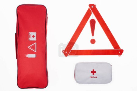 Photo for Flat lay with automotive handbag, first aid kit and warning triangle isolated on white - Royalty Free Image