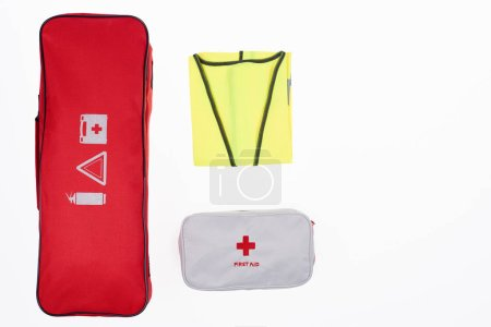 flat lay with automotive handbag, first aid kit and reflective vest isolated on white