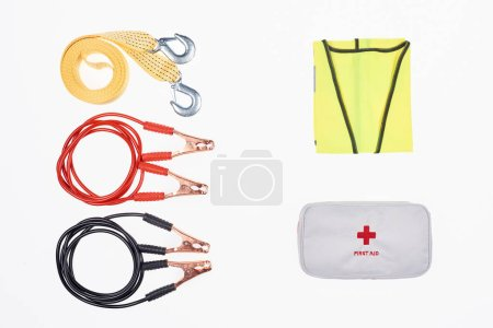 flat lay with car tow rope, jump start cables, first aid kit and reflective vest isolated on white