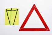 top view of warning triangle and reflective vest isolated on white