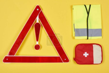 top view of warning triangle road sign, first aid kit and reflective vest isolated on yellow