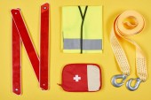 flat lay with arranged first aid kit and automotive accessories isolated on yellow