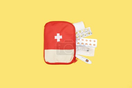 top view of automotive first aid kit with different medicines isolated on yellow
