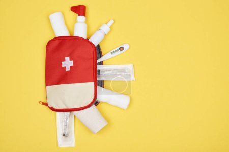 Photo for Top view of first aid kit with various medicines isolated on yellow - Royalty Free Image