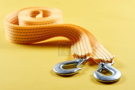 close up view of car tow rope on yellow background