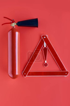 top view of fire extinguisher and warning triangle isolated on red