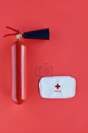top view of fire extinguisher and first aid kit isolated on red