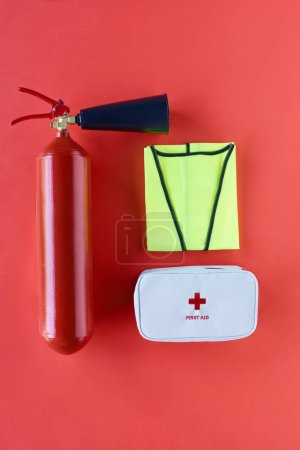 top view of fire extinguisher, reflective vest and first aid kit on red backdrop
