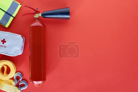 top view of fire extinguisher and automotive accessories on red backdrop