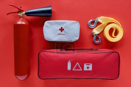 flat lay with fire extinguisher, automotive handbag, first aid kit and car tow rope on red backdrop