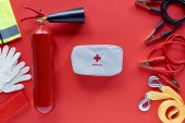 flat lay with fire extinguisher, first aid kit and automotive accessories on red background