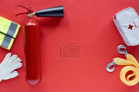 Photo for Flat lay with fire extinguisher, first aid kit and automotive accessories on red background - Royalty Free Image