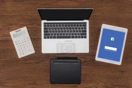 Photo for Top view of laptop with blank screen, calculator, textbook and digital tablet with facebook on screen - Royalty Free Image