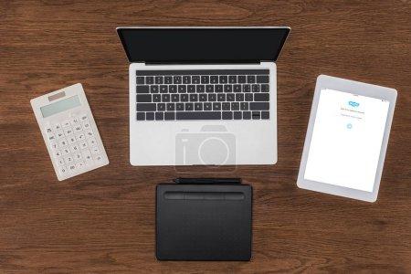 Photo pour Vue de dessus sur écran d'ordinateur portable avec écran blanc, calculatrice, manuel et tablette numérique avec Skype - image libre de droit