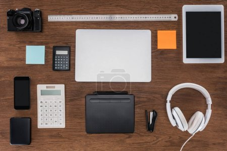 top view of workplace with laptop, ruler, photo camera, smartphone and digital tablet on wooden table