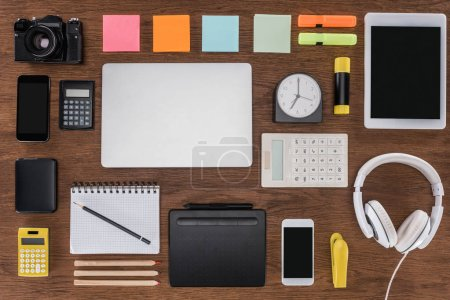 top view of arranged workplace with smartphones, laptop, digital tablet, photo camera and stationery