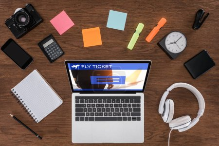 top view of wooden table with empty textbook, smartphone, photo camera and laptop with fly ticket on screen