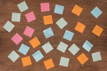 top view of arranged colorful post it notes on wooden table