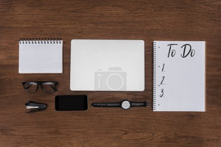 top view of workplace with arranged laptop, wristwatch, smartphone and textbook with lettering to do on wooden table