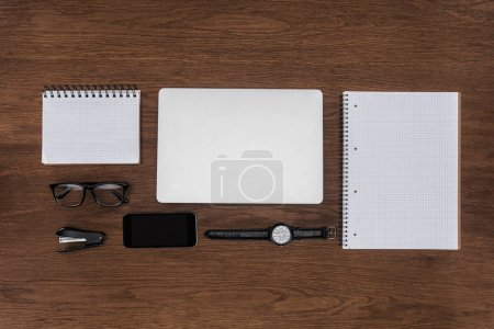top view of workplace with arranged empty textbooks, laptop, wristwatch and smartphone on wooden table