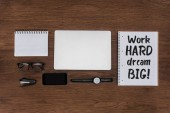 top view of workplace with arranged laptop, wristwatch, smartphone and textbook with lettering work hard dream big on wooden table