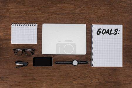 Foto de Vista superior del lugar de trabajo con ordenador portátil arreglado, reloj, smartphone y libro de texto con letras objetivos en mesa de madera - Imagen libre de derechos