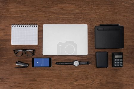 Photo for Top view of workplace with arranged empty textbook, laptop, wristwatch and smartphone with facebok on screen - Royalty Free Image