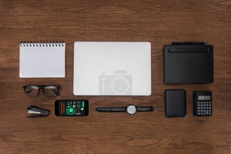 top view of workplace with arranged empty textbook, laptop, wristwatch and smartphone with marketing analysis on screen