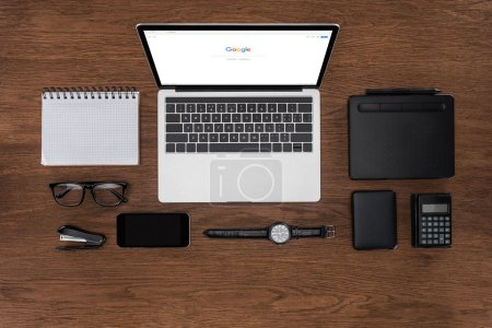 Photo for Top view of workplace with arranged empty textbook, smartphone, wristwatch and laptop with google on screen - Royalty Free Image