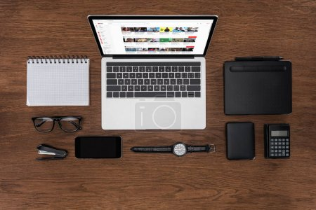 Photo for Top view of workplace with arranged empty textbook, smartphone, wristwatch and laptop with youtube on screen - Royalty Free Image