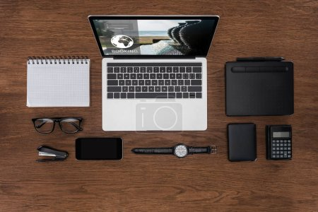 top view of workplace with arranged empty textbook, smartphone, wristwatch and laptop with booking on screen