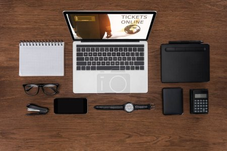top view of workplace with arranged empty textbook, smartphone, wristwatch and laptop with tickets online on screen