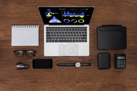 top view of workplace with arranged empty textbook, smartphone, wristwatch and laptop with graphics on screen