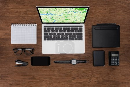top view of workplace with arranged empty textbook, smartphone, wristwatch and laptop with map on screen